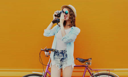 Happy young woman with film camera and bicycle on an orange background