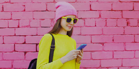 Portrait of young woman with phone in the city over a pink wall background Foto de archivo