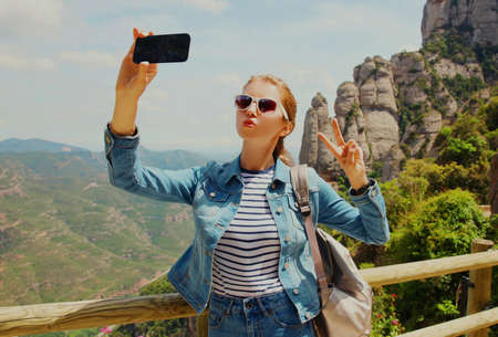 Travel image young woman taking selfie picture by smartphone on a mountain Montserrat background
