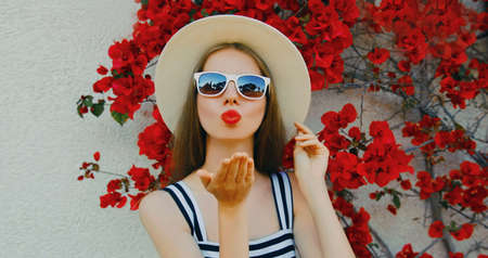 Portrait of beautiful woman blowing red lips sending sweet air kiss wearing a summer straw hat on a red flowers background