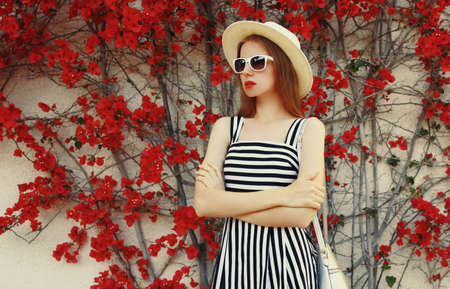 Portrait of beautiful woman wearing a summer straw hat on a red flowers background