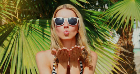 Summer portrait young woman blowing her lips sending air kiss on a beach, palm tree background