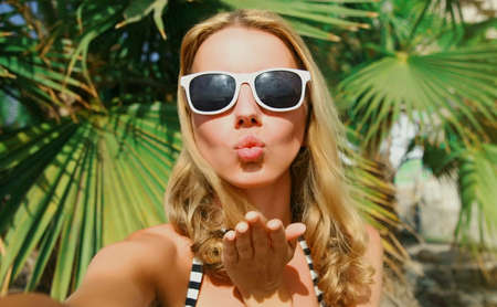 Summer portrait close up of woman stretching hand for taking selfie blowing lips sending sweet air kiss on a beach, palm tree background Stok Fotoğraf