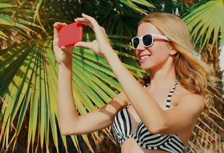 Summer portrait of happy smiling woman taking selfie picture by smartphone on a beach, palm tree background