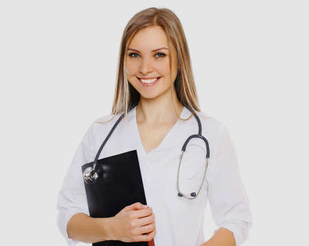 Portrait of friendly woman doctor with stethoscope and folder of documents on a white background