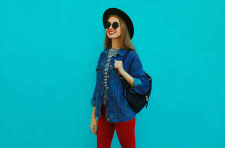Portrait of smiling young woman wearing a black round hat, denim jacket and backpack on a blue background