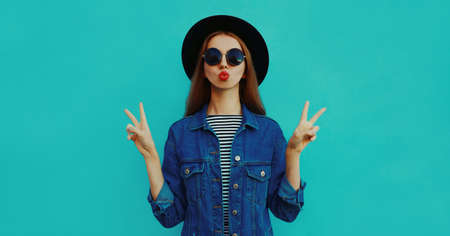 Portrait of young woman blowing her red lips sending air kiss wearing a black round hat, denim jacket on a blue background