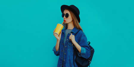 Portrait of young woman drinking a juice wearing a black round hat, denim jacket on a blue background