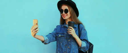 Portrait of stylish woman taking selfie picture by smartphone wearing a black hat, backpack on a blue background