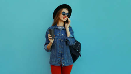 Portrait of smiling young woman calling on a phone wearing a black round hat, denim jacket on a blue background