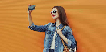 Portrait of smiling woman taking a selfie picture by smartphone wearing a denim jacket on a orange background