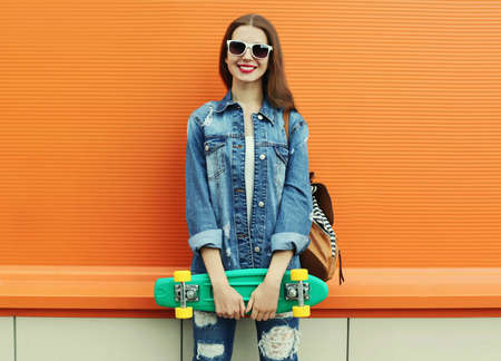 Portrait of smiling young woman with green skateboard on a colorful orange background Stok Fotoğraf
