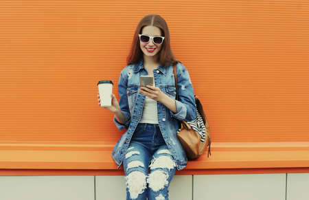 Portrait of smiling young woman with smartphone wearing a denim jacket on a orange background