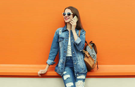 Portrait of smiling young woman calling on a smartphone wearing a denim jacket on a orange background Stok Fotoğraf