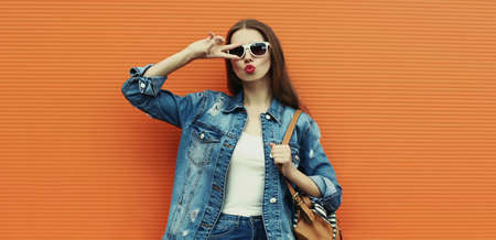 Portrait of young woman wearing a denim jacket with backpack posing on a orange background