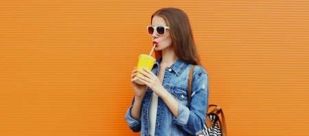 Portrait of young woman drinking a juice on a orange background