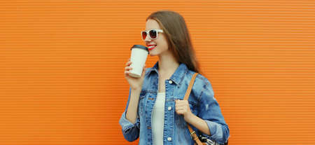 Portrait of happy smiling young woman with cup of coffee in a city on a orange background Stok Fotoğraf