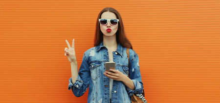 Portrait of young woman with smartphone wearing a denim jacket posing on a orange background Stok Fotoğraf