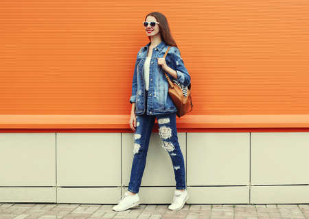 Portrait of smiling young woman wearing a denim jacket and jeans with backpack on a orange background Stok Fotoğraf
