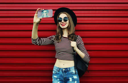 Portrait of smiling woman taking a selfie picture by smartphone on a red background Stok Fotoğraf