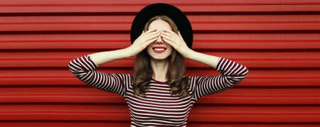 Portrait of happy young woman covering her eyes with her hands wearing a black round hat on a red background