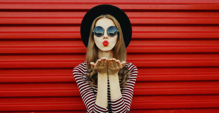 Portrait of stylish young woman blowing her red lips sending air kiss wearing a black round hat on a background Stok Fotoğraf