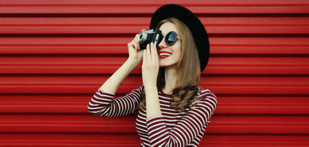 Portrait of happy young woman photographer with vintage film camera on a red background