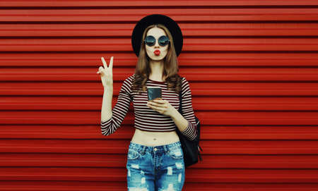 Portrait of stylish young woman with smartphone on a red background