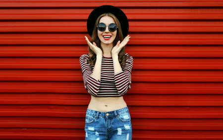 Portrait of happy excited young woman wearing a black round hat and sunglasses on a red background