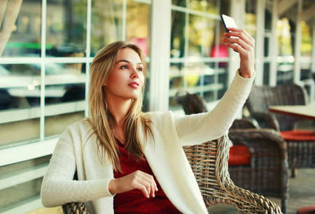 Portrait of young woman taking selfie picture by smartphone sitting at a table in a cafe Stok Fotoğraf