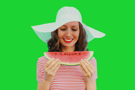 Portrait of happy smiling young woman with slice of watermelon on a green background