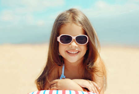 Summer close up portrait of happy smiling little girl child lying on sand beach Stok Fotoğraf