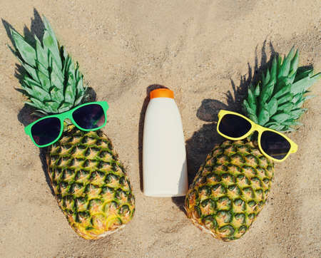 Close up of summer two funny pineapple in colorful sunglasses and sunscreen skin bottle on a beach Stok Fotoğraf