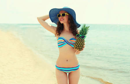 Portrait of happy young woman on a beach with funny pineapple wearing a straw hat on a sea background Stok Fotoğraf