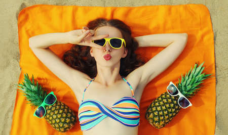 Portrait of young woman lying on a beach with funny pineapple wearing a sunglasses