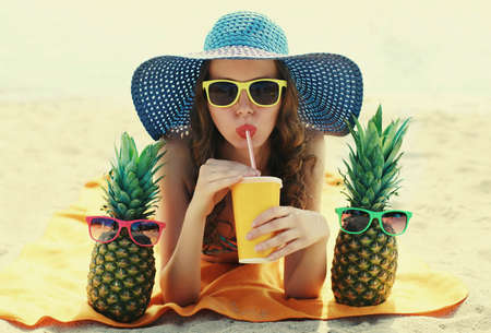 Portrait of young woman drinking a juice lying on a beach with funny pineapple wearing a straw hat