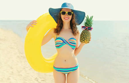 Summer portrait of happy smiling woman with inflatable circle and pineapple wearing a straw hat on a beach, sea background