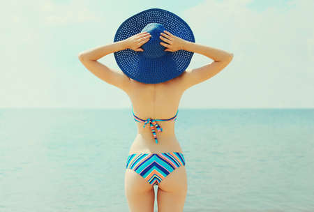 Rear view of beautiful young woman on a beach wearing a straw hat and bikini over a sea background
