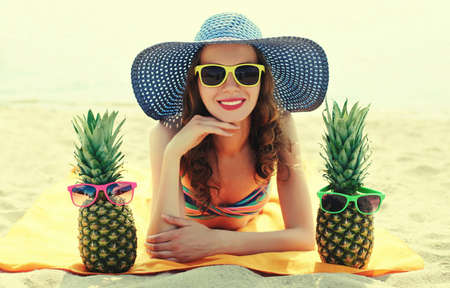 Portrait of happy smiling young woman lying on a beach with funny pineapple wearing a straw hat Stok Fotoğraf