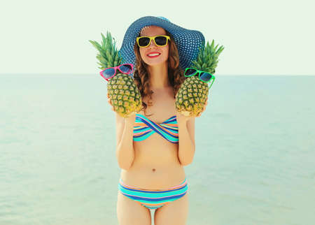 Portrait of happy smiling young woman on a beach with funny pineapple wearing a straw hat
