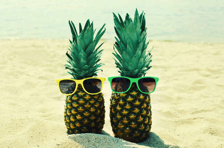Close up of summer two funny pineapple in colorful sunglasses on a beach