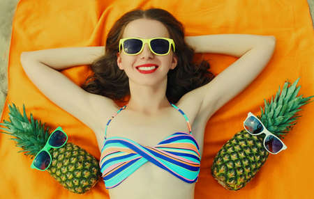 Portrait of happy smiling young woman lying on a beach with funny pineapple wearing a sunglasses