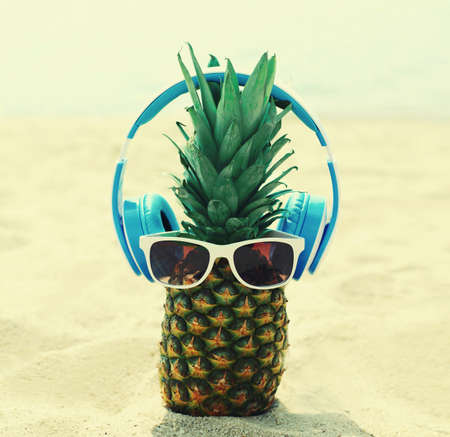 Close up of summer pineapple listening to music in headphones and sunglasses on a beach