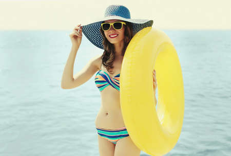 Summer portrait of happy smiling woman with inflatable circle wearing a straw hat on a beach, sea background
