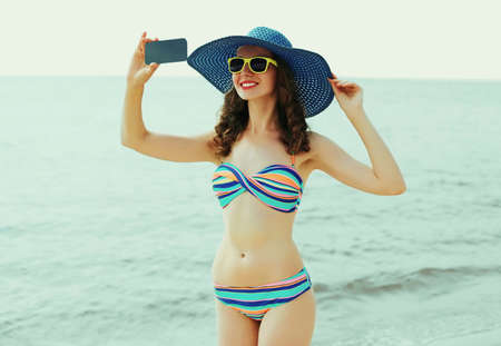 Beautiful young woman taking a selfie picture by smartphone on a beach wearing a straw hat and bikini on a sea background at summer day