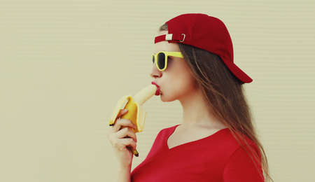 Portrait of woman eating banana on a white background