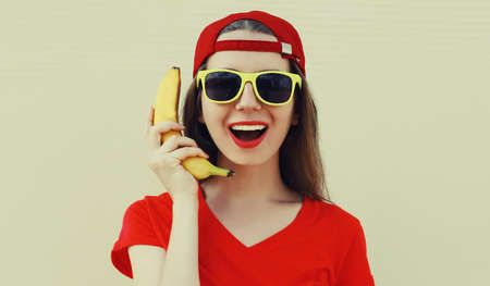 Portrait of funny woman calling on a banana phone on a white background Stok Fotoğraf