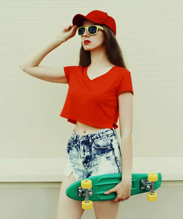 Summer portrait of young woman with green skateboard wearing a shorts and red baseball cap in a city