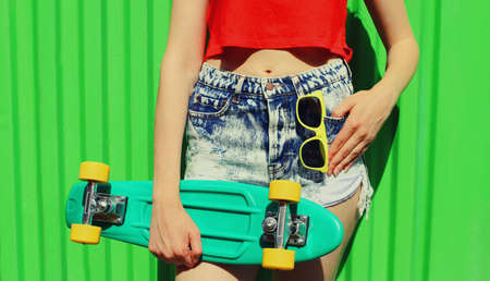 Close up woman holding green skateboard in shorts on a green background Stok Fotoğraf