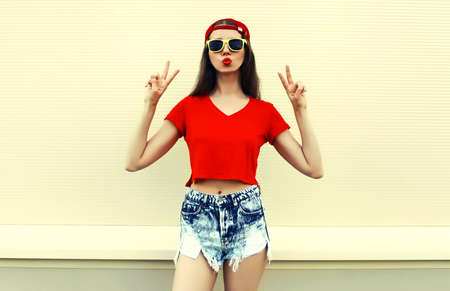 Portrait of young woman model wearing a red baseball cap, t-shirt and shorts on a background